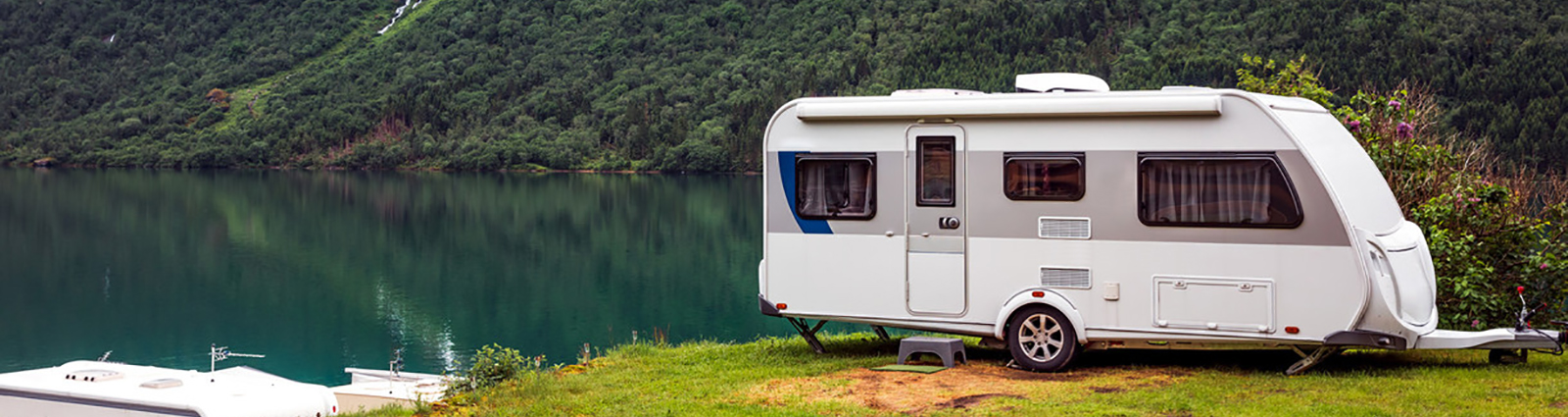 Small camper van outside by a lake